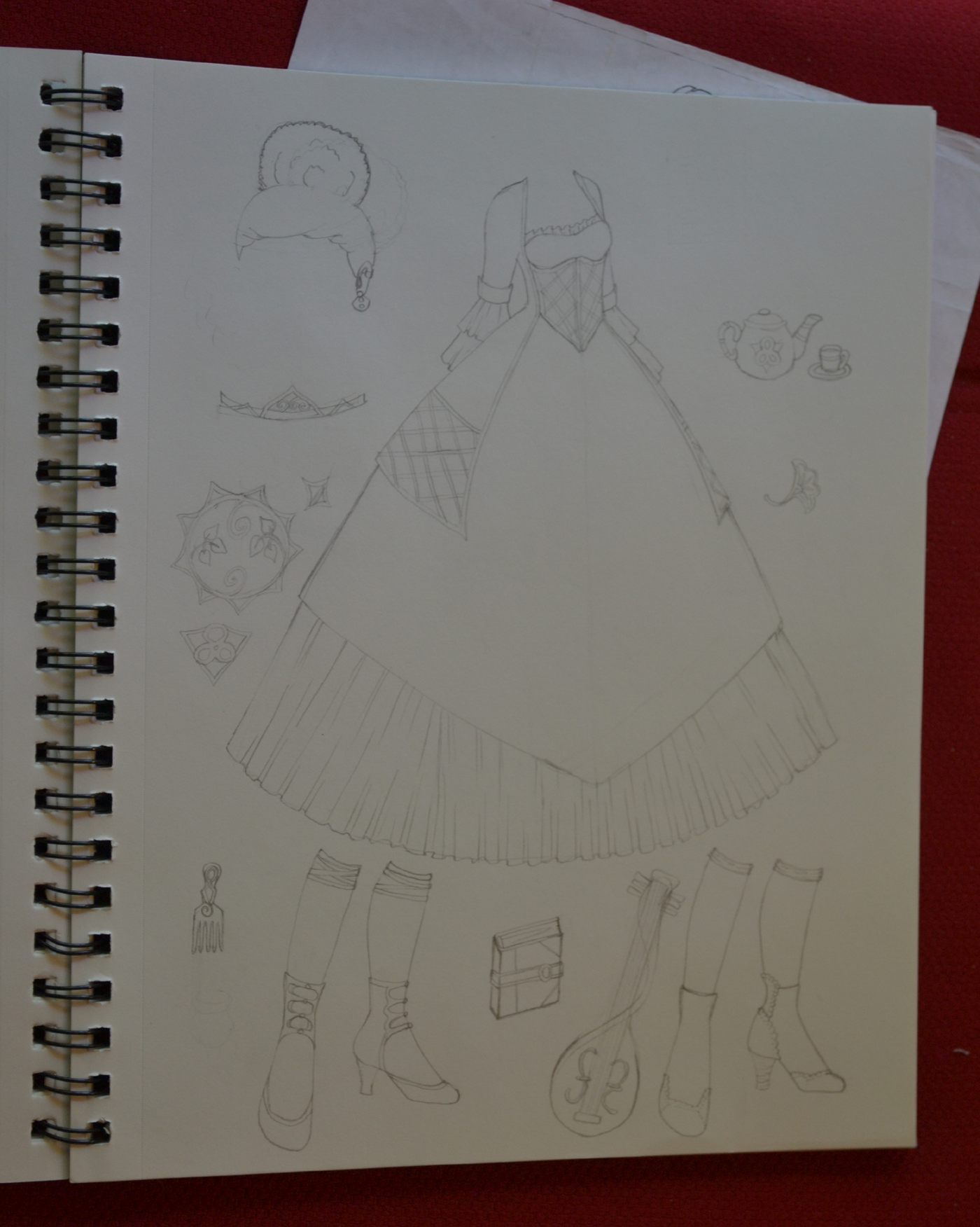 A penciled in sketch of a princess gown, crown, wig, instrument and two pairs of shoes. These penciled sketches are then inked to create a version for scanning.