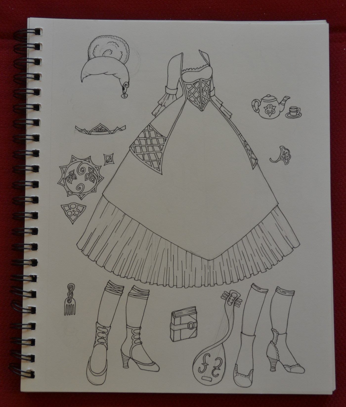 The inked sketch of a princess gown, wig, accessories, shoes and a tea set. The pattern elements that will eventually make up the skirt are on the far left side of the page.
